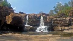 Man meditates in a waterfall Stock Footage