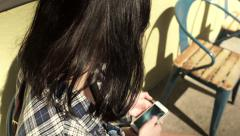 Teen Sits Outside Coffee Shop And Play With Her Smart Phone (Slow Motion) Stock Footage