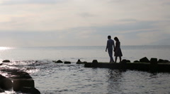 Guy and girl walk on rocks in sea and kiss at dawn Stock Footage
