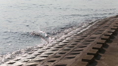 Water moves waves towards concrete river bank Stock Footage