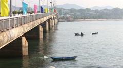Fisherman in boat fishes with landing-net near bridge Stock Footage
