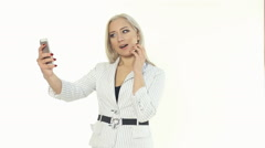 Business woman in a white jacket making selfie photo on the phone on a white Stock Footage