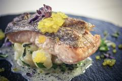 Salmon fillet with Jeruzalem artichokes, roasted spinach and orange caviar - stock photo