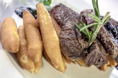 Deer backstrap on pine needles, honey onion and potato puree - stock photo