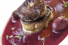 Grilled foie gras in cinnamon cherry soup with walnut bread Stock Photos