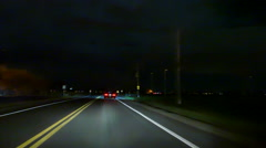 Car driving towards a glowing house fire at night - Commercial licensing Stock Footage