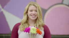 Teen Hols Bouquet Flowers And Smiles, In Front Of Colorful Mural (Slow Motion) Stock Footage