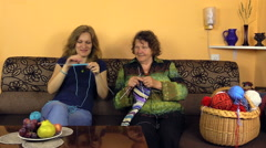Happy old grandma knit with nurse girl on sofa in nursing home Stock Footage