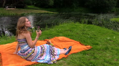 Woman drink cider champagne alcohol sitting on plaid near river Stock Footage