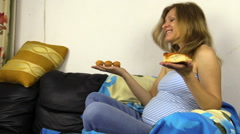 Hungry pregnant woman make decision what to eat. Bun or cakes. Stock Footage