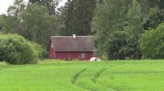 Rural grange homestead house between fields and trees. Zoom in Stock Footage