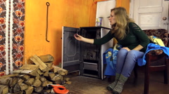 Woman with woolen socks close old stove door and leave the room Stock Footage