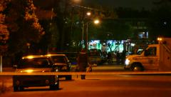 SWAT officers walking at crime scene at night with ambulance - Commercial Stock Footage