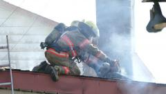 Firemen using power tools and water hose on building rooftop - Commercial Stock Footage