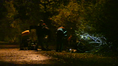 Paramedics and police doing CPR in dark walking path - Commercial licensing Stock Footage