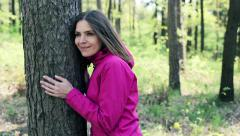 Young, pretty woman hugging a tree in the forest  HD Stock Footage