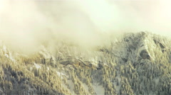 Snow fall over trees and mountains at sunset - stock footage