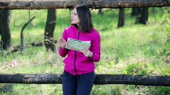 Young, pretty woman reading a map in the country fence HD - stock footage
