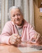Old sad woman at home - stock photo