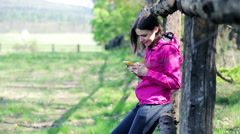 Young, pretty woman with a smartphone in the country fence  HD - stock footage