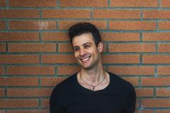 Stock Photo of Stylish casual smiling man lean back brick wall.