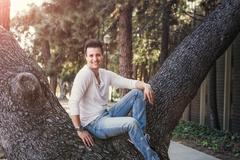Handsome casual happy man sitting on tree. Stock Photos