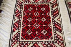 Stock Photo of Rug handmade with black pattern on red background