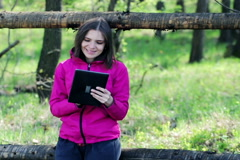Young, pretty woman with a tablet siting in the country fence NTSC - stock footage