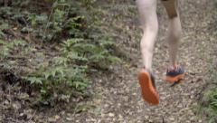 Closeup Of Runner's Legs As He Runs Past Camera On Forest Trail (4K) Stock Footage
