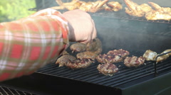 Man, flipping burgers on a barbeque grill Stock Footage