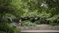 Man Runs Down And Then Up A Set Of Stairs In A Picturesque Park, Shot In 4K Stock Footage
