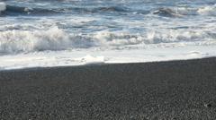 Waves breaking at black sand beach Stock Footage