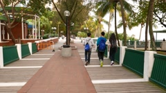 Friends walk on sea-front walkway at park, boy stumble on ground Stock Footage