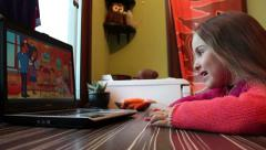 Little girl watching a animation movie on laptop computer, Model release Stock Footage