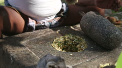 Man sitting and grinding seeds on a traditional grinding stone. Stock Footage