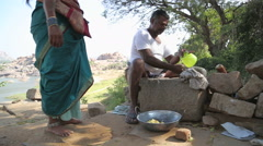 Man sitting and grinding seeds on the traditional grinding stone. Stock Footage