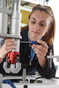 Apprentice Female Engineer Working On Machine In Factory Stock Photos