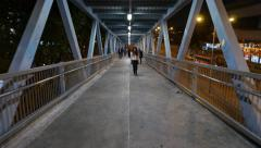 Walking down long ramp, pedestrian overpass, night outdoors aside Stock Footage