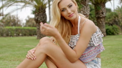 Blond Woman in Summer Clothes Sitting on Grass Stock Footage