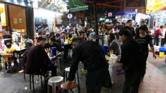 Extremely crowded street eatery area, road restaurants in night time Stock Footage