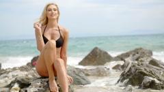 Blond Woman in Bikini Sitting on Boulder on Beach Stock Footage
