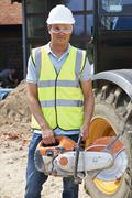 Construction Worker On Site Holding Circular Saw Stock Photos