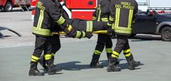 brave Firefighters carry a fellow firefighter with the stretcher - stock photo
