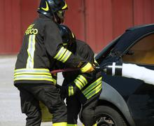 Two firemen in action with foam to put out the fire of the car Stock Photos