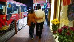 Lovely chinese couple walking small busy street in night, chase camera Stock Footage