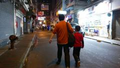 Chinese man walking with son at night street, chasing camera behind the pair Stock Footage