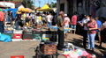 Antiques, old merchandise at the flea market. People at street market, Brazil. Footage