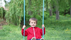 Adorable little boy, swinging happily in the park, daytime - stock footage