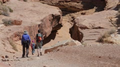 A family hiking through a desert wash slot canyon Stock Footage