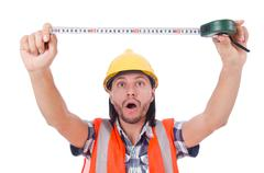 Stock Photo of Construction worker with tape-line isolated on white